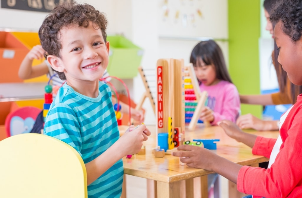 stock-photo-kindergarten-students-smile-when-playing-toy-in-playroom-at-preschool-international-education-698288386