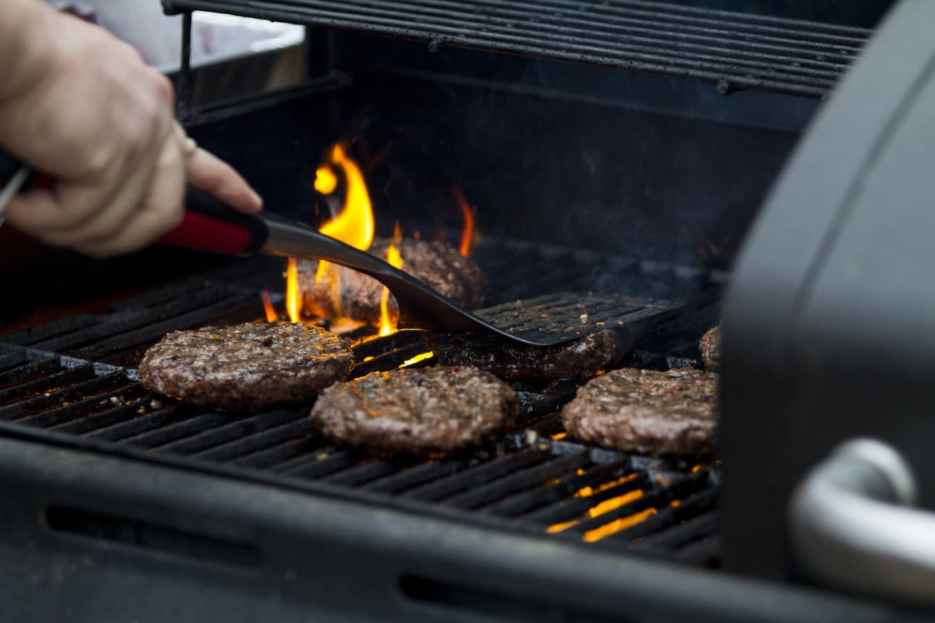 A man grilling burgers on a grille outside